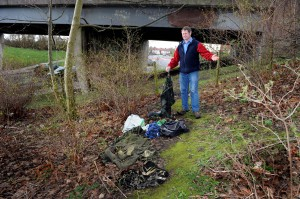 Clean-up call: City councillor Robert Betton, who represents Botcherby in Carlisle, pictured with rubbish which has built up under the Eastern Way bridge over Durranhill Road